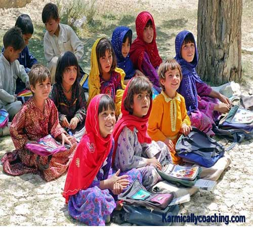 Little children attending a school class under a tree